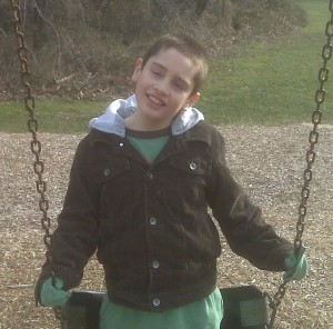 young boy with autism playing on a swing
