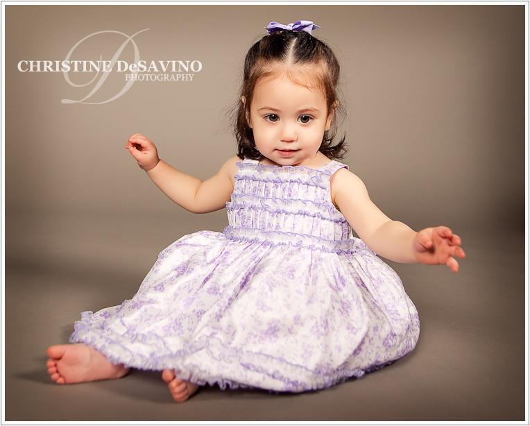 Studio portrait of a sweet little girl in a beautiful purple flowered dress