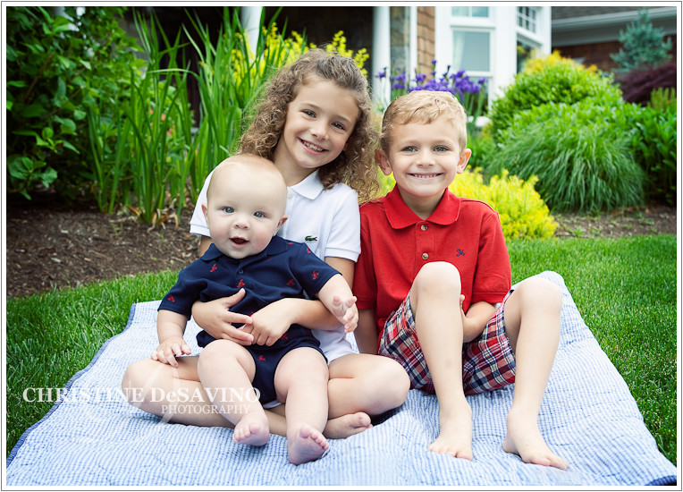 Adorable family on a blanket on the lawn in front of a beautiful home
