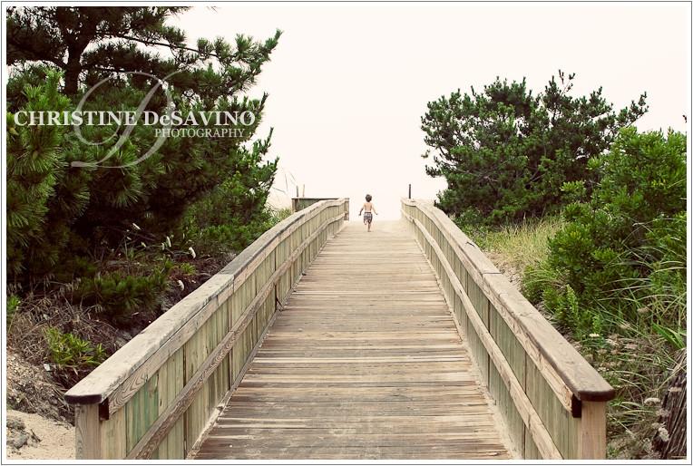boy runs down the boardwalk to the ocean, lbi nj