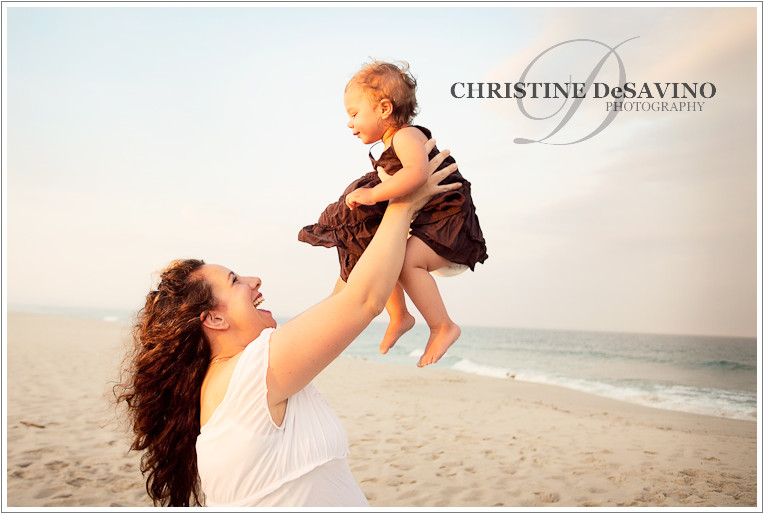 Beautiful mom holding baby daughter in the air on the beach along the ocean