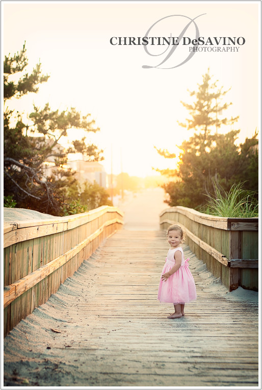 Baby girl on the boardwalk along the beach during golden sunset on LBI