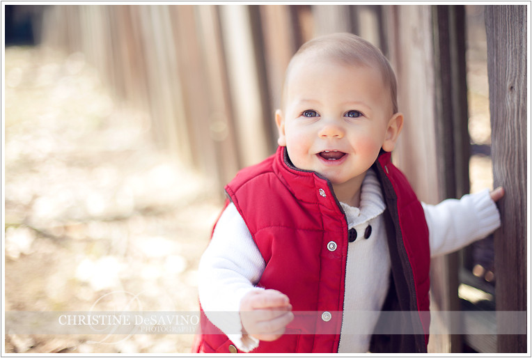 Boy in red vest holding fence - NJ Child Photographer