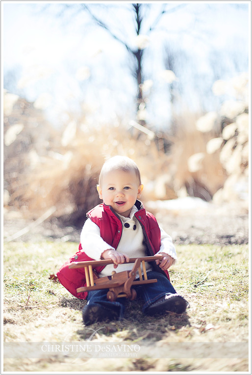Boy in red vest holding wooden airplane - NJ Child Photographer