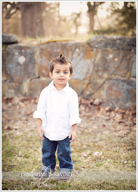 Adorable boy stands by stone wall - NY Child Photographer