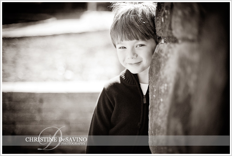 Black and white of boy peaking from behind a stone wall - NJ Child Photographer