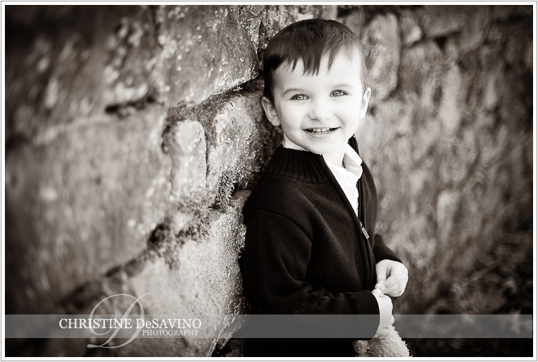 Black and white image of boy leaning against stone wall smiling - NJ Child Photographer