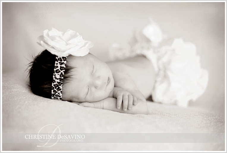 Black and white of sleeping newborn girl with leopard skin bow - NJ Newborn Photographer