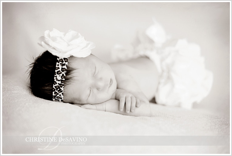 Beautiful newborn wears flower head with leopard skin band - NJ Baby Photographer