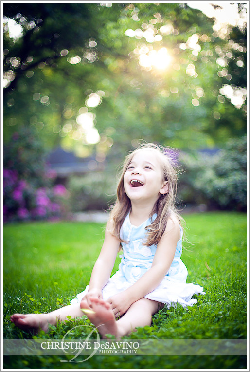 Girl on lawn laughing - NJ Child Photographer